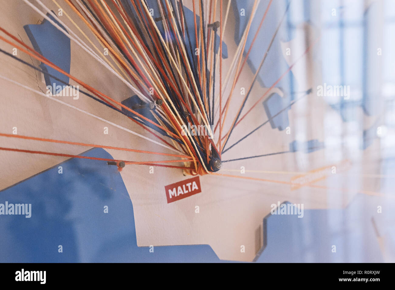 Abstract colored threads stretched on pins on map, depicting flight directions from Malta around World. Logistic grid, geometric, connections, isometrics and spirograph concept - Stock Image