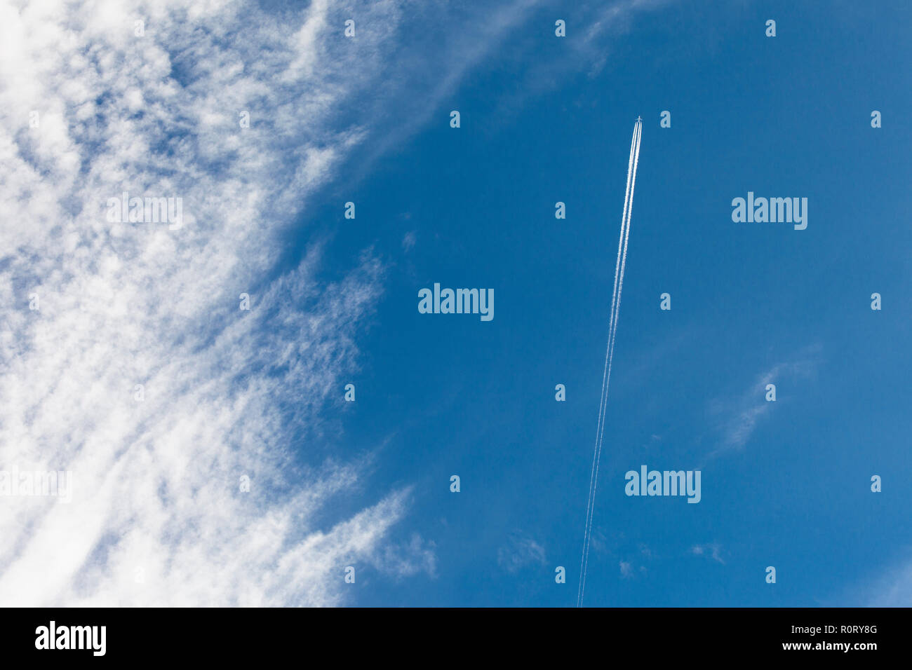 A passenger airplane leaving a vapour trail - Stock Image
