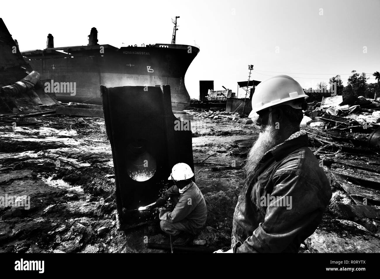Labourers  work at ship- breaking yard. Bangladesh is dependent on ship-breaking industry for 80% of its steel needs. Chittagong, Bangladesh. - Stock Image