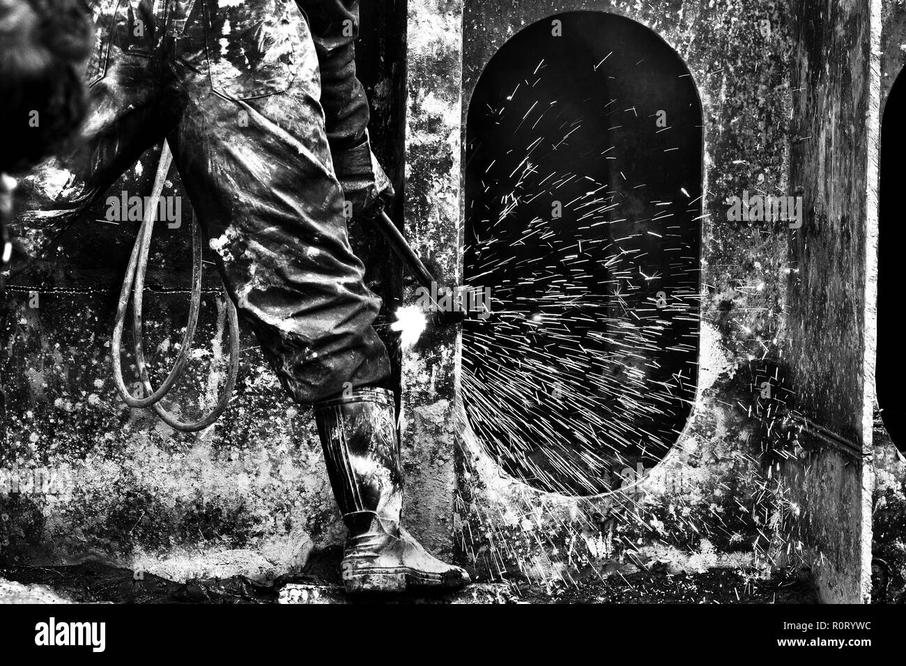 Labourer works at ship- breaking yard. Bangladesh is dependent on ship-breaking industry for 80% of its steel needs. Chittagong, Bangladesh. - Stock Image