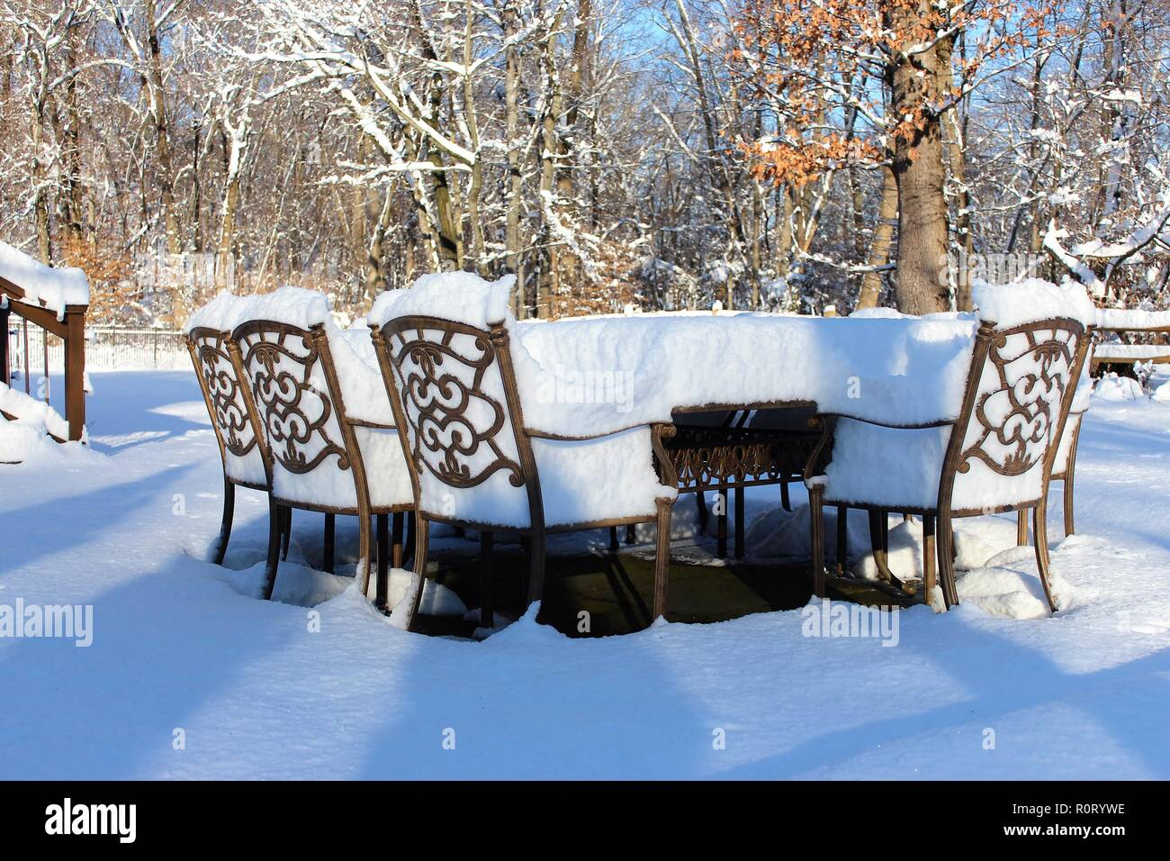 Outdoor table and chairs covered by snow - Stock Image