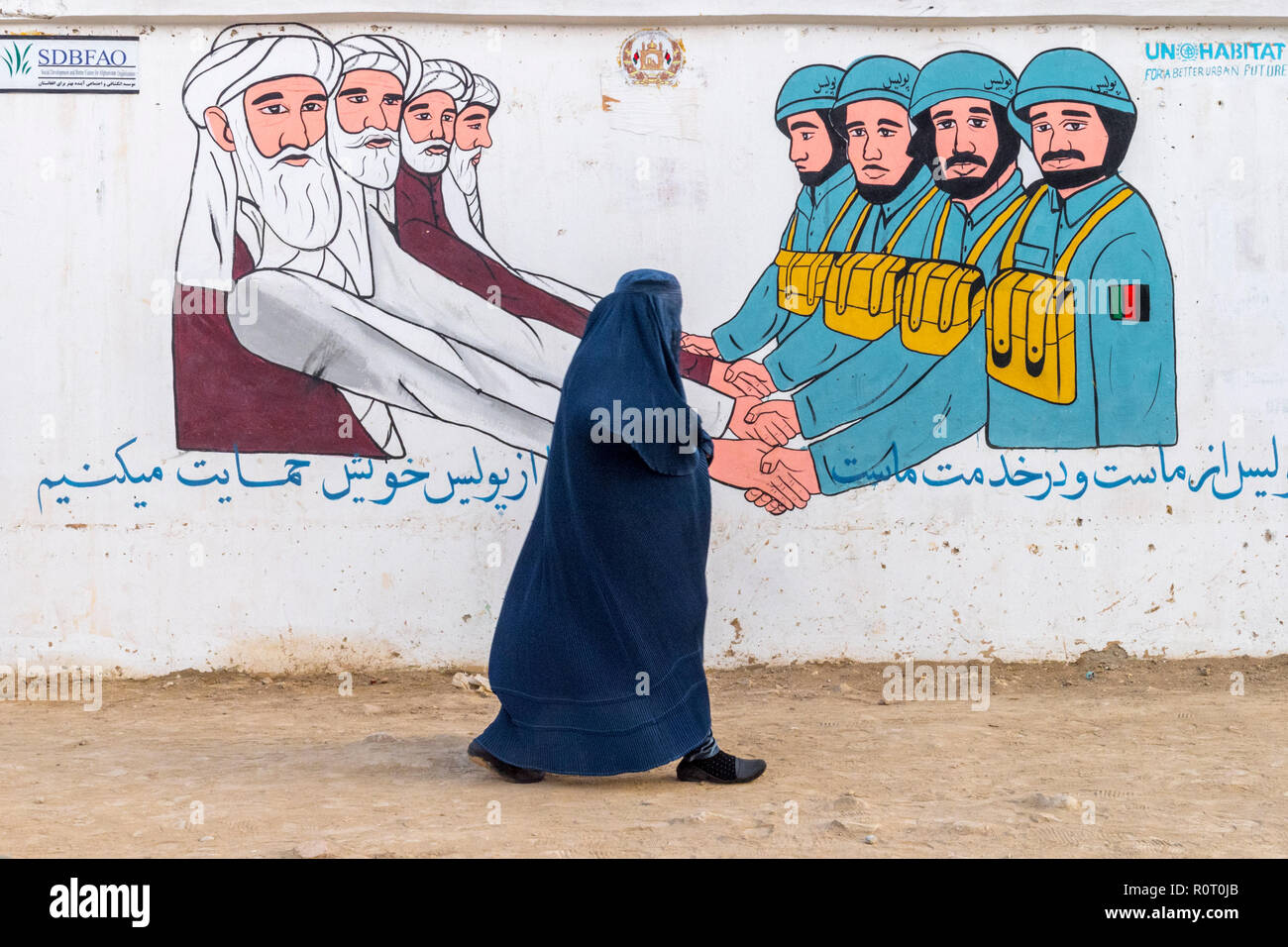 Woman Walking By Sponsored Naive Propaganda Mural On The Street Side About The Army And The Clerics Caring Of The People, Mazar-e Sharif, Afghanistan Stock Photo