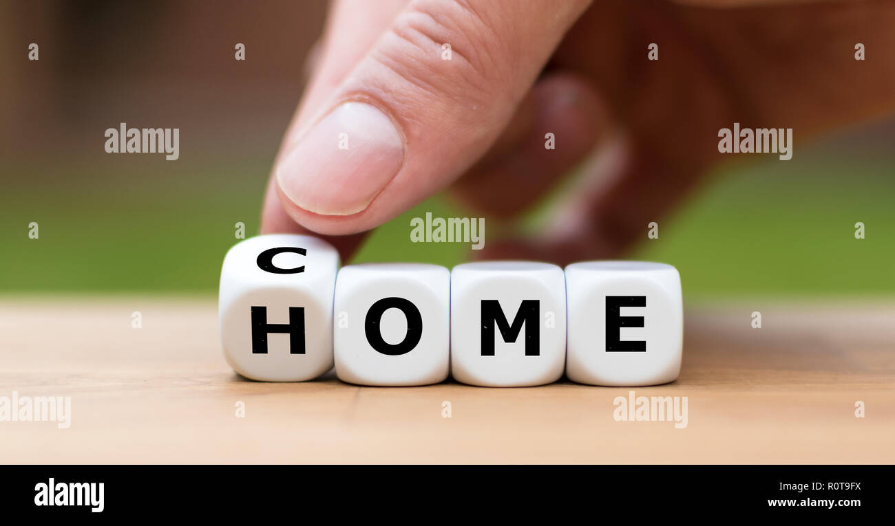 Hand is turning a dice and changes the word 'come' to 'home' - Stock Image