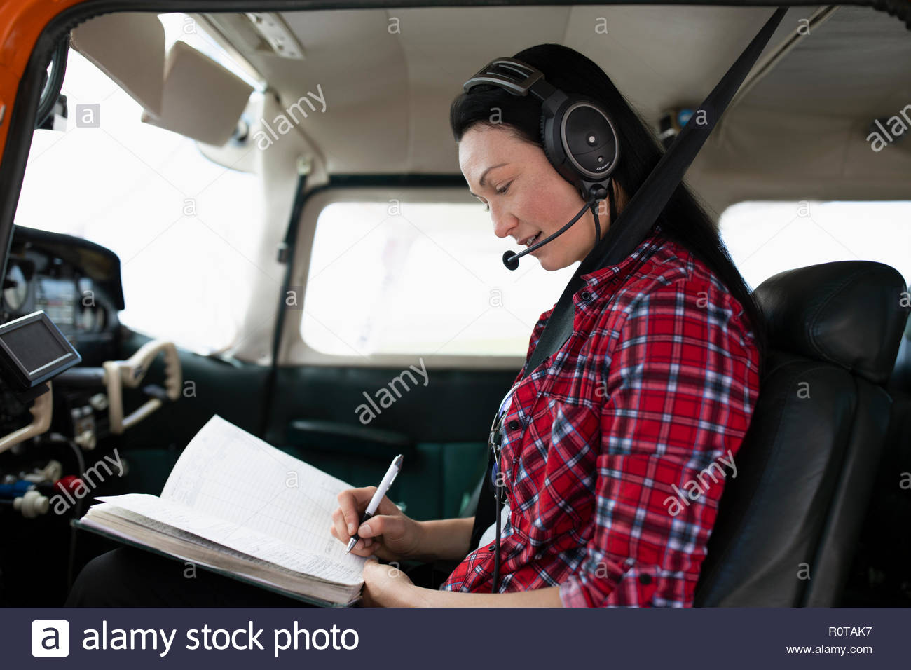 Female pilot filling out log book in airplane cockpit - Stock Image