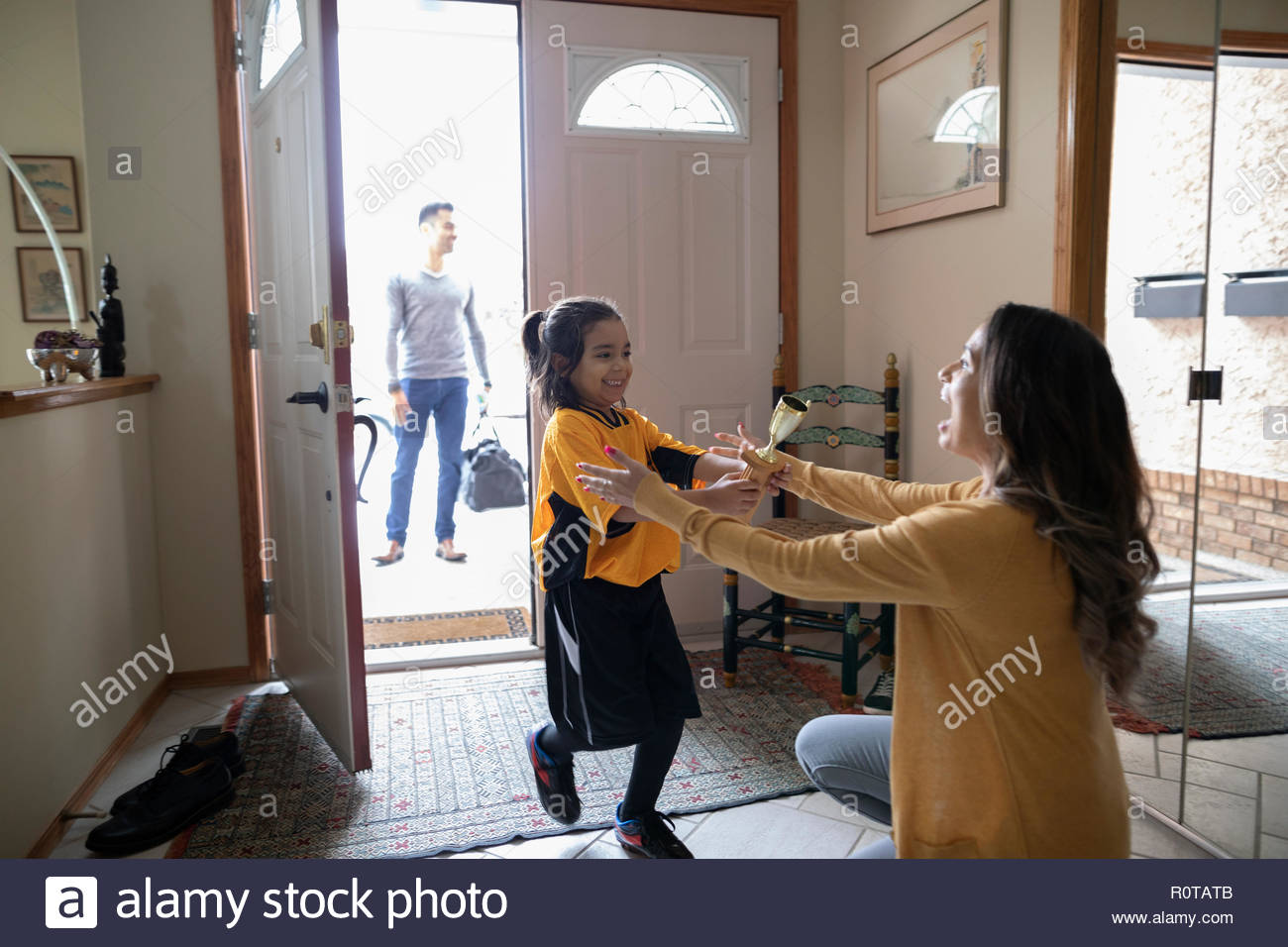 Mother greeting excited son in soccer uniform with trophy Stock Photo