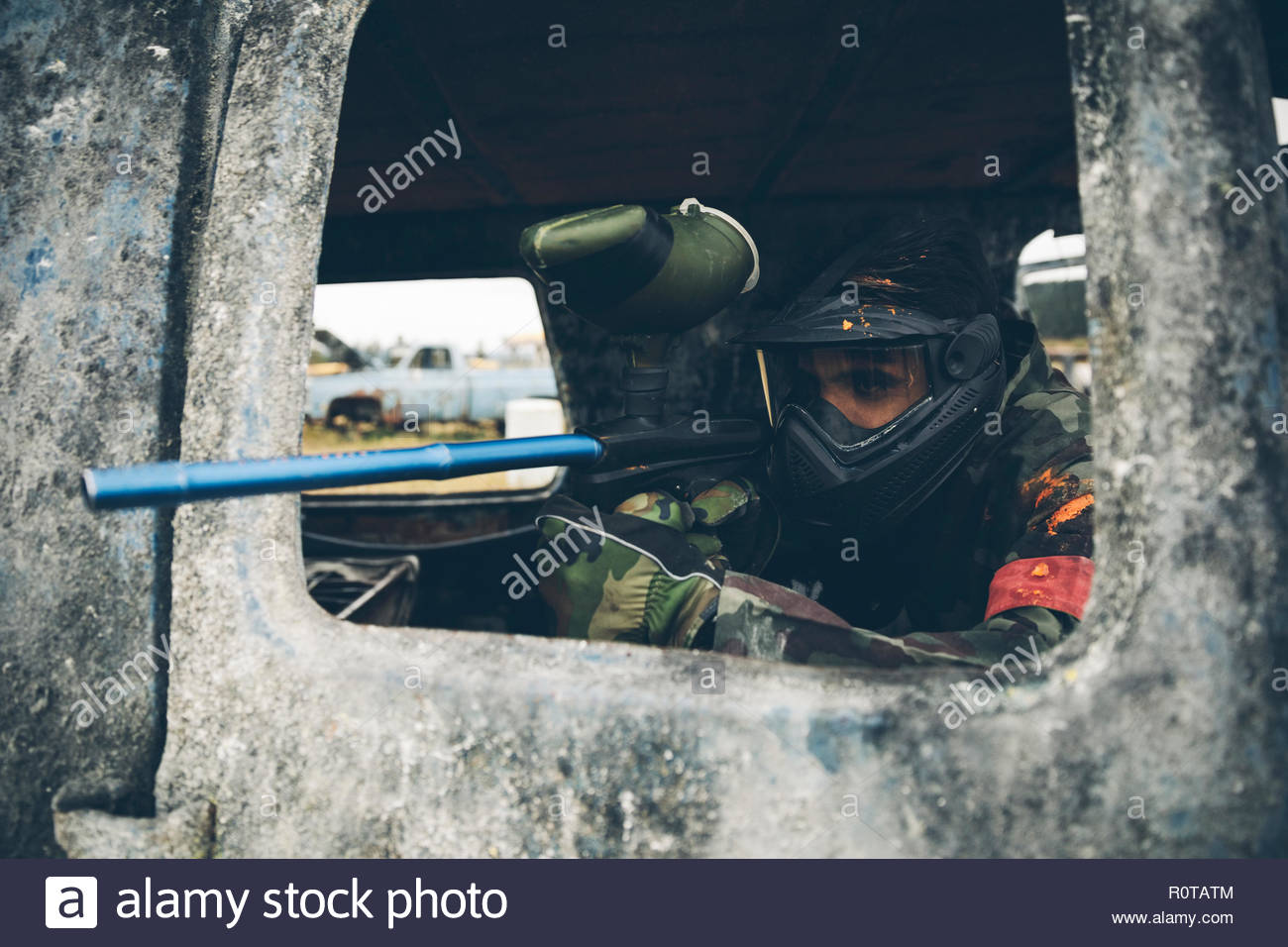 Man in rusted car paintballing - Stock Image
