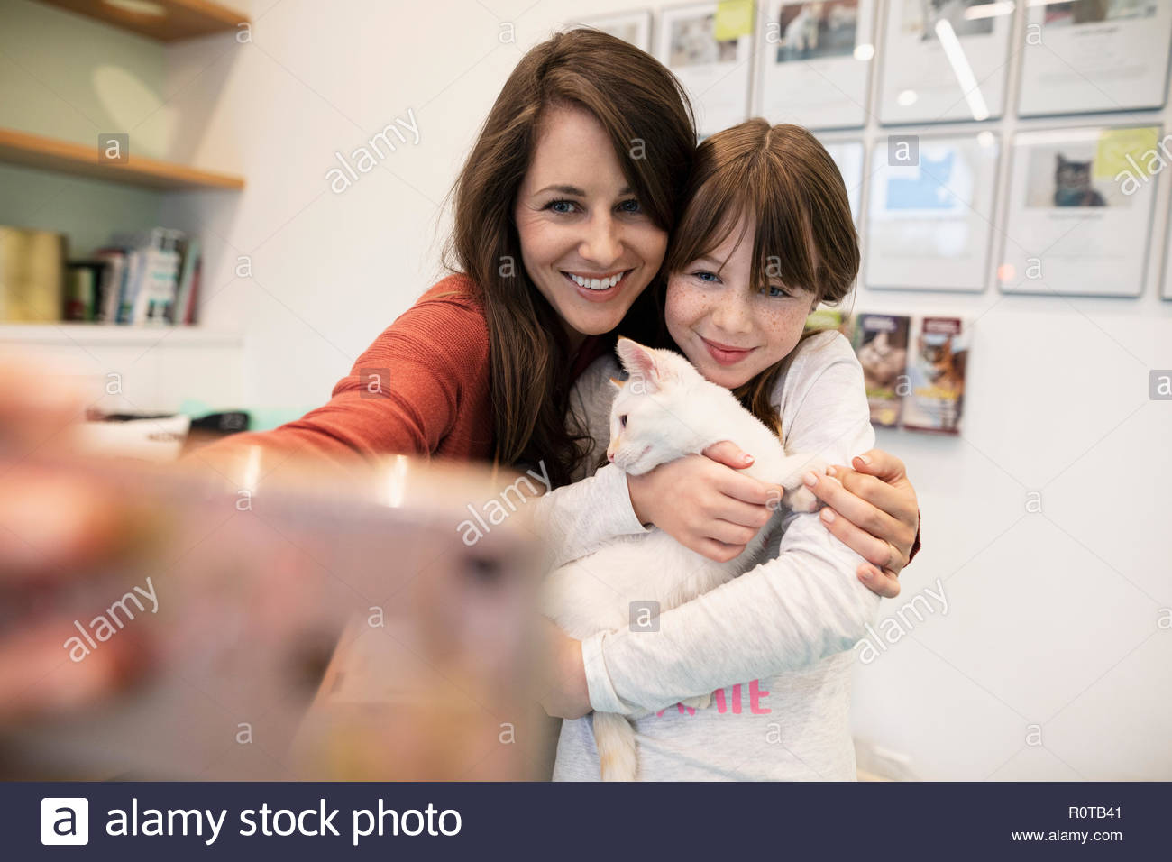 Mother and daughter holding kitten and taking selfie with smart phone in animal shelter - Stock Image