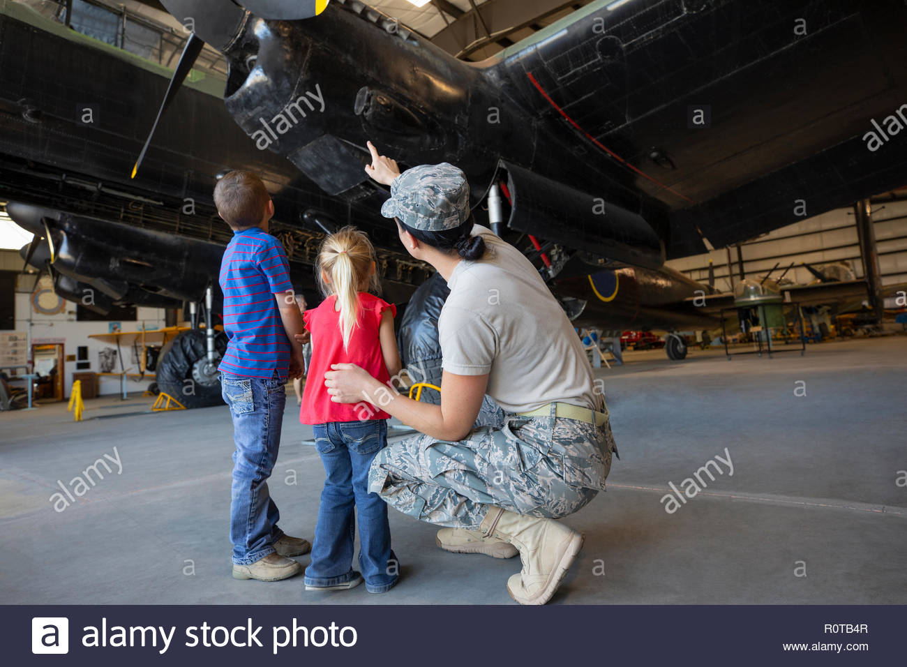 Female army engineer mother showing airplane to children in airplane hangar - Stock Image