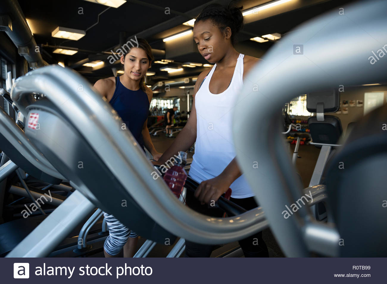 Female personal trainer guiding woman using treadmill in gym - Stock Image