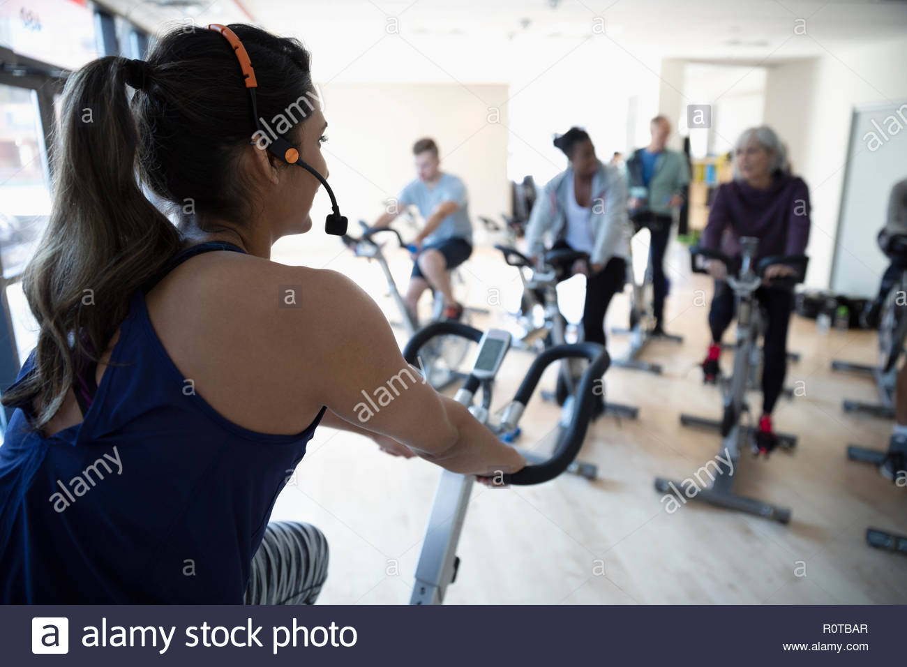 Female instructor riding exercise bike in spin class in gym - Stock Image
