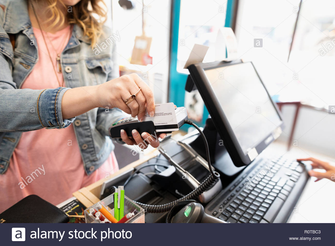 Female shopper paying with credit card, using credit card reader in shop - Stock Image