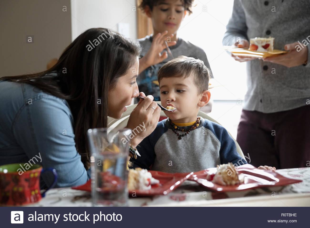 Latinx mother feeding birthday cake to toddler son - Stock Image