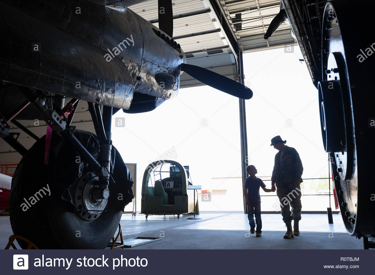 Female army engineer mother walking with son in military airplane hangar - Stock Image