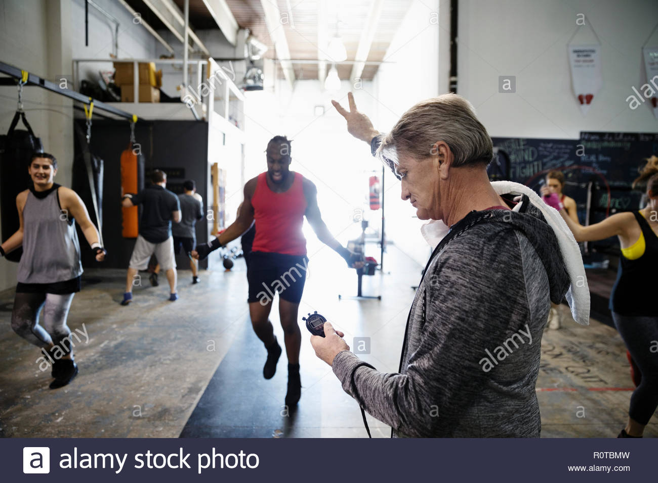 Trainer with stopwatch timing male boxers jump roping in gym - Stock Image