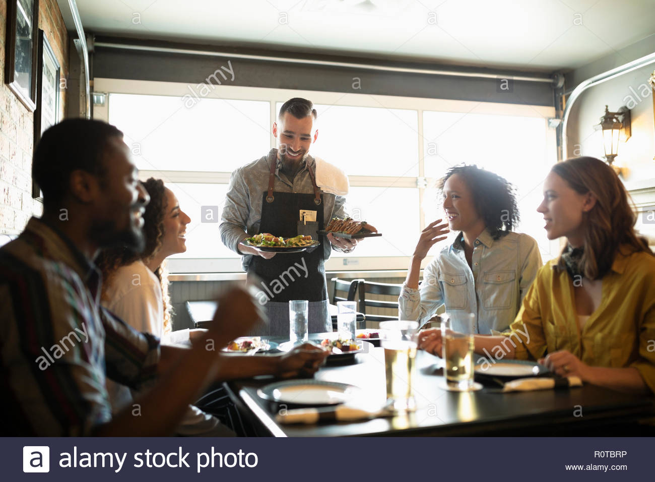 Waiter serving food to friends in bar - Stock Image