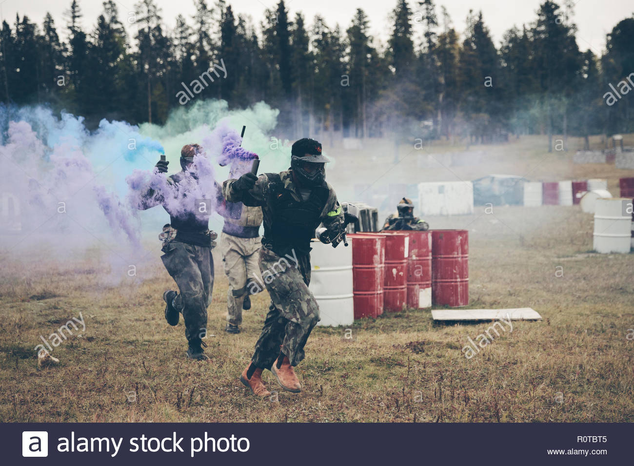 Paintballing team with smoke bombs running in field - Stock Image