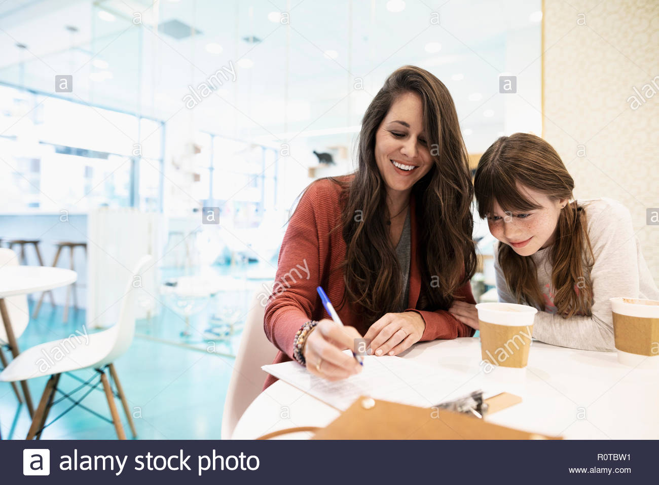 Smiling mother and daughter drinking coffee and filling out adoption application in cat cafe - Stock Image