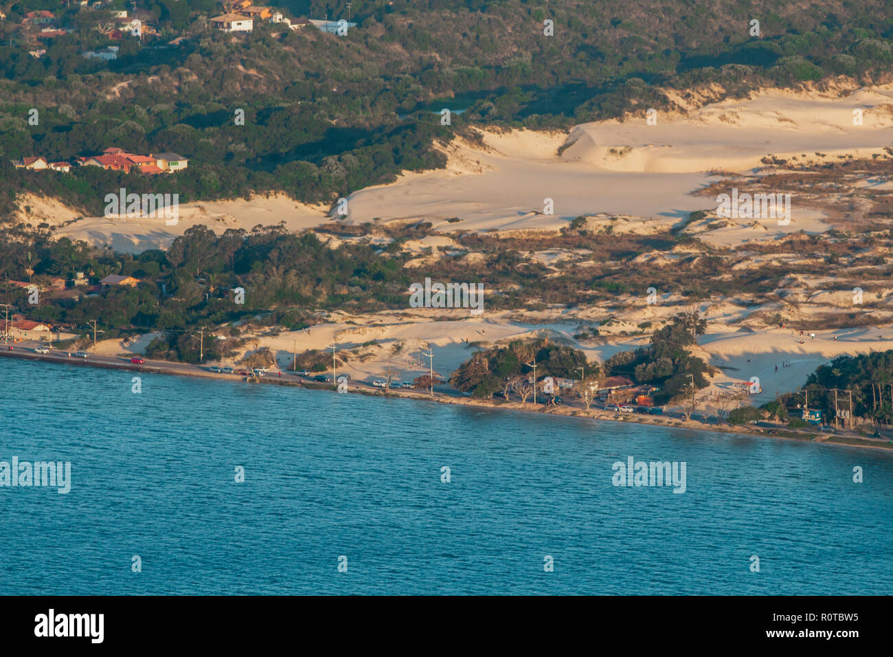 blue water and dunes separated by a thin road at Florianopolis, Santa Catarina, Brazil - Stock Image