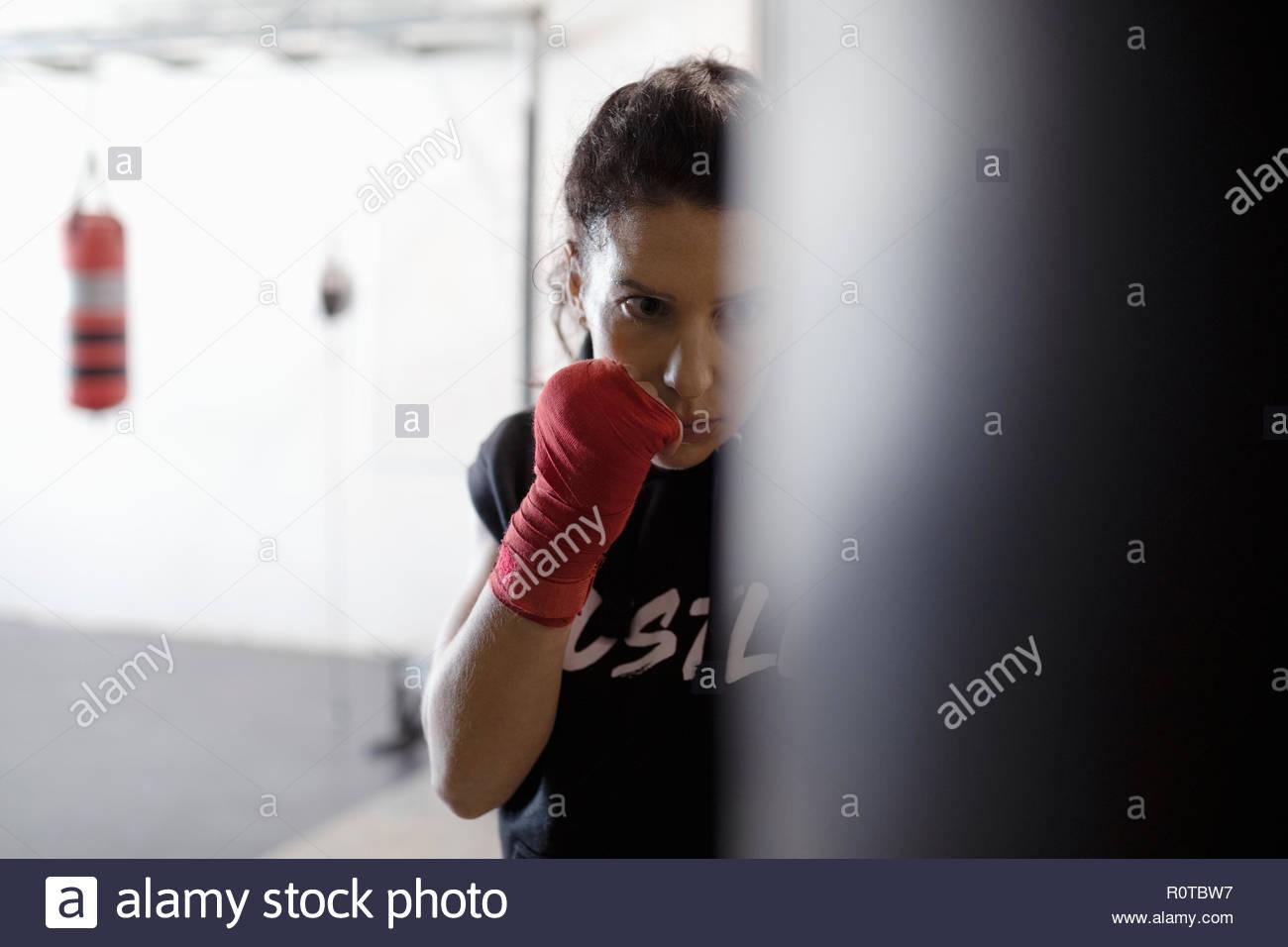 Tough, focused female boxer training at punching bag in gym - Stock Image
