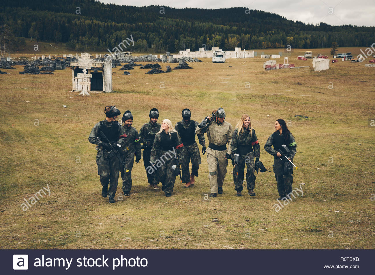 Friends walking out to paintballing field - Stock Image