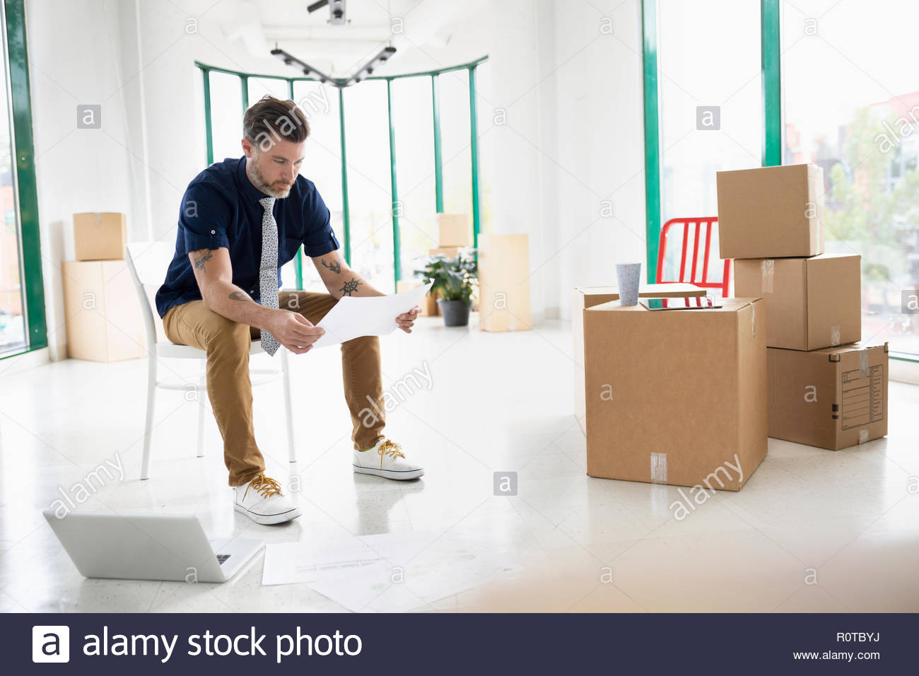 Businessman with laptop and blueprints in new, empty office space with cardboard boxes - Stock Image