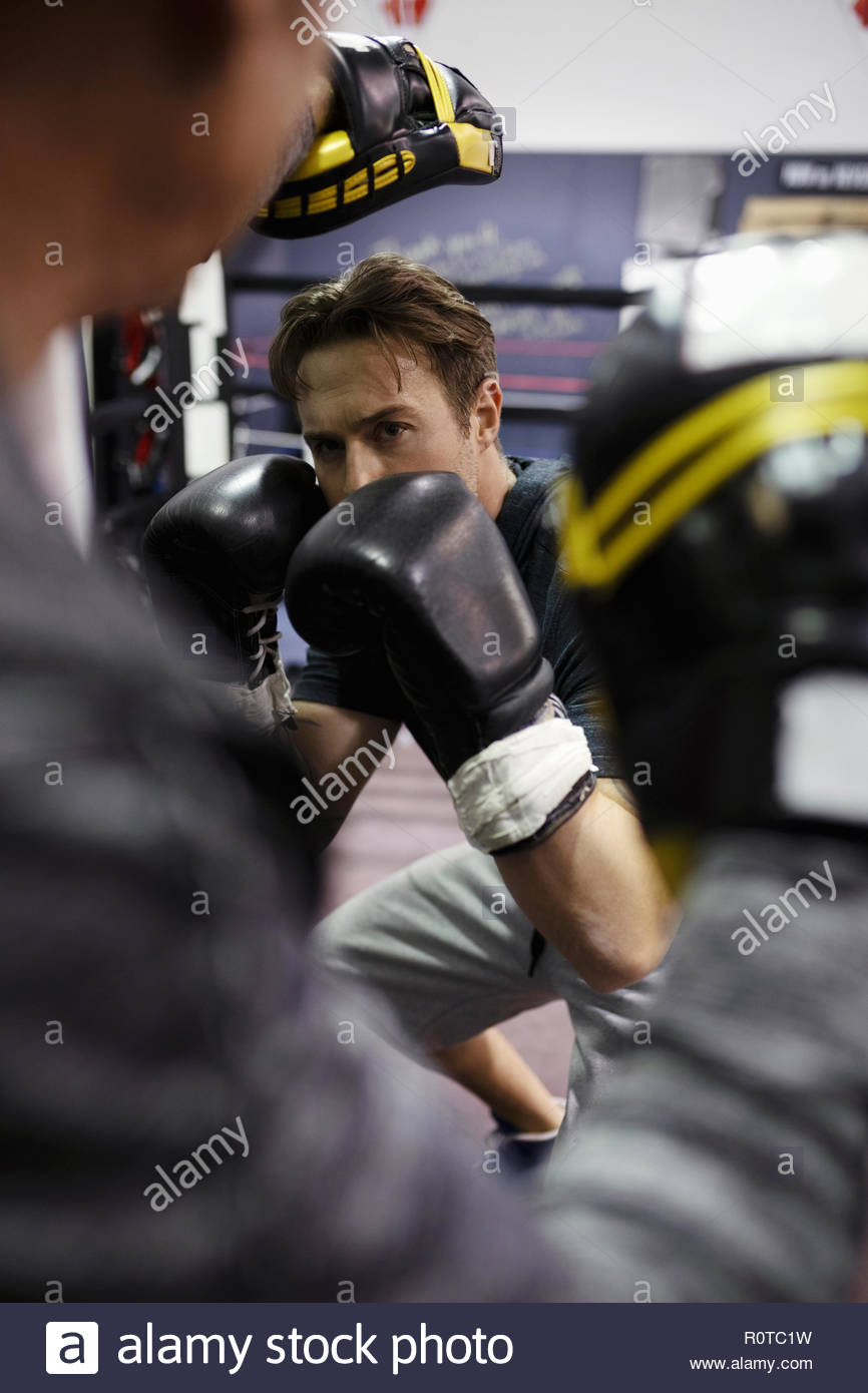 Focused male boxer training in gym - Stock Image