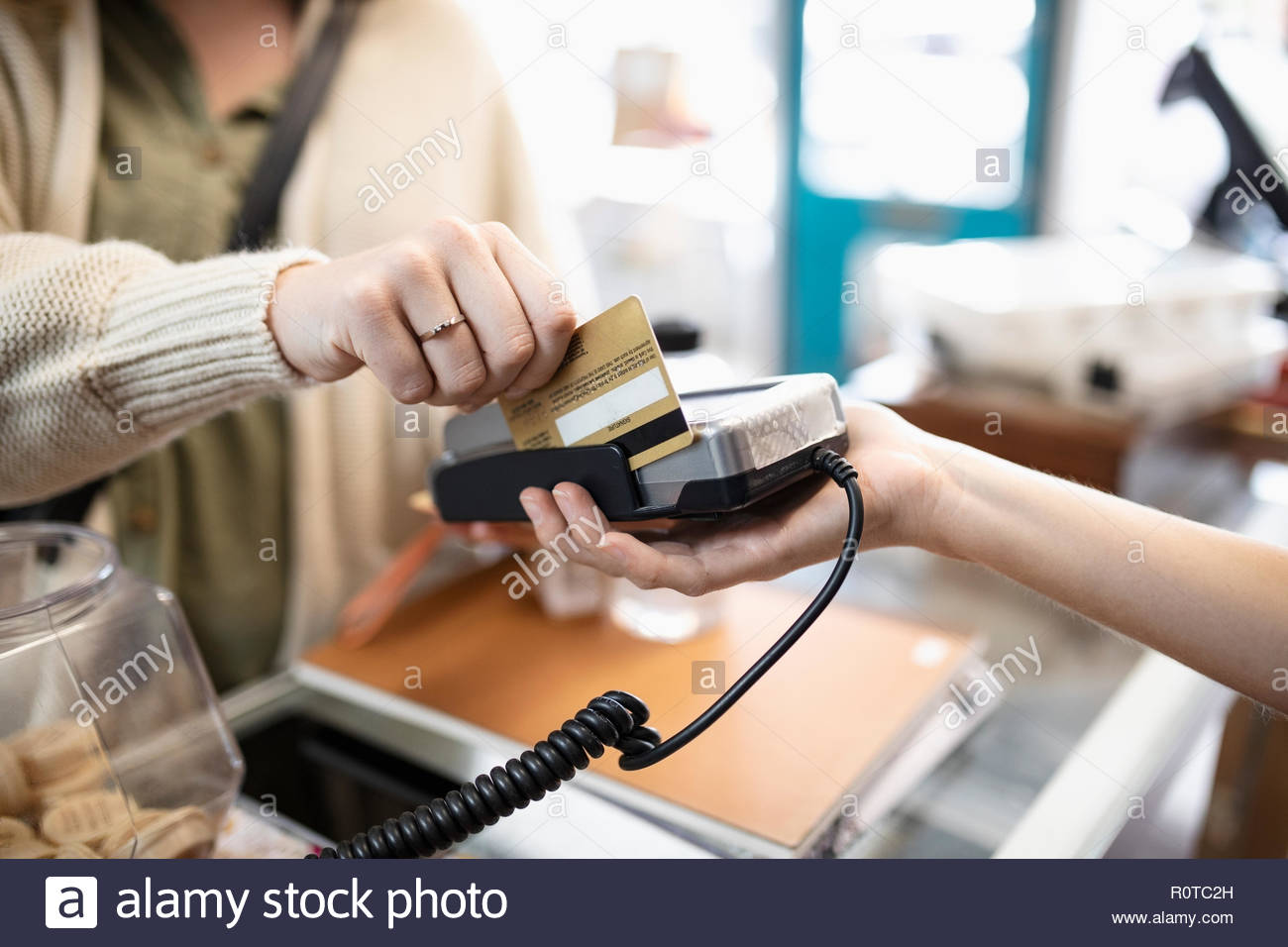 Close up female shopper paying, using credit card reader in shop - Stock Image
