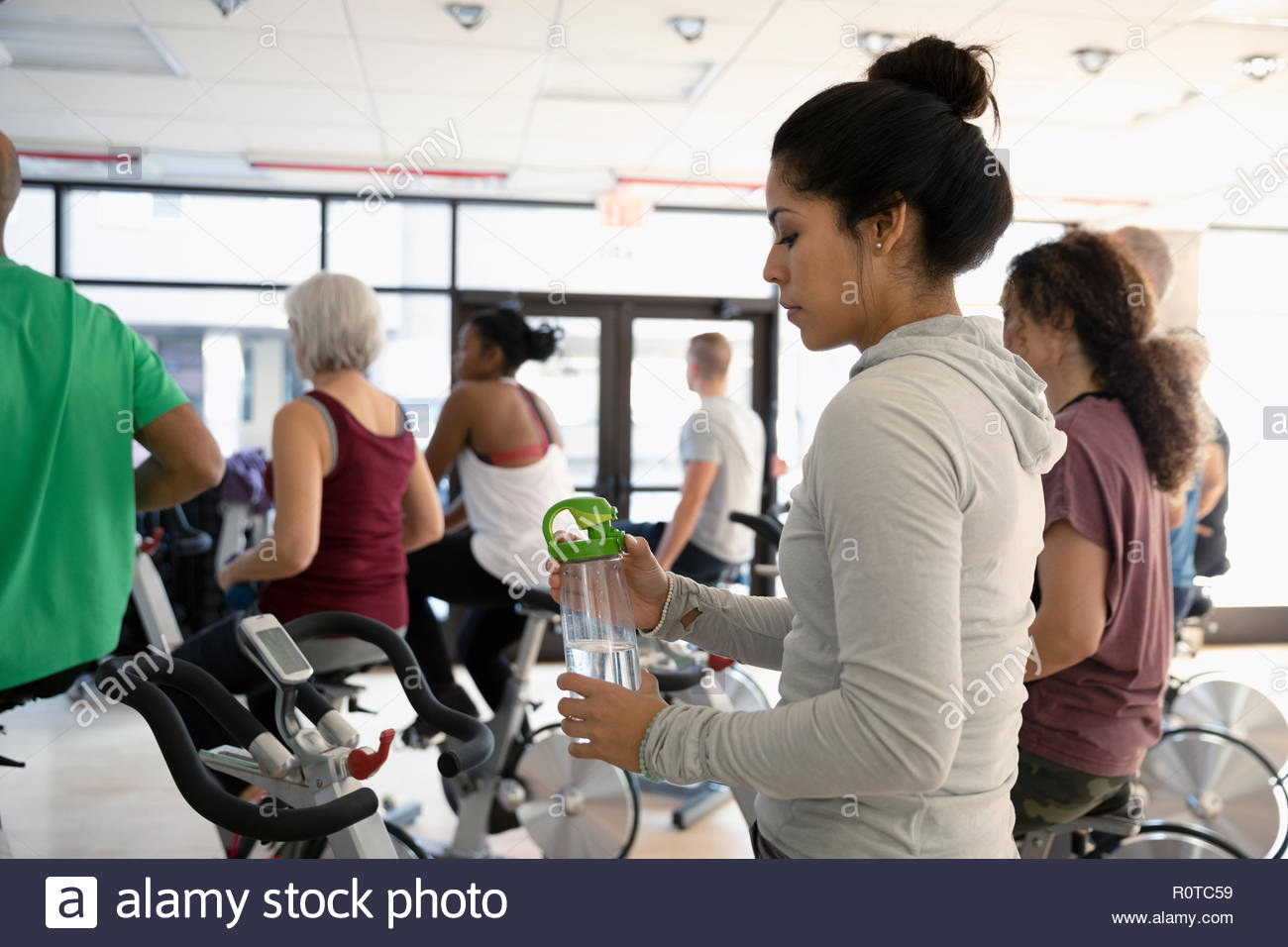 Woman with water bottle preparing for spin class in gym - Stock Image