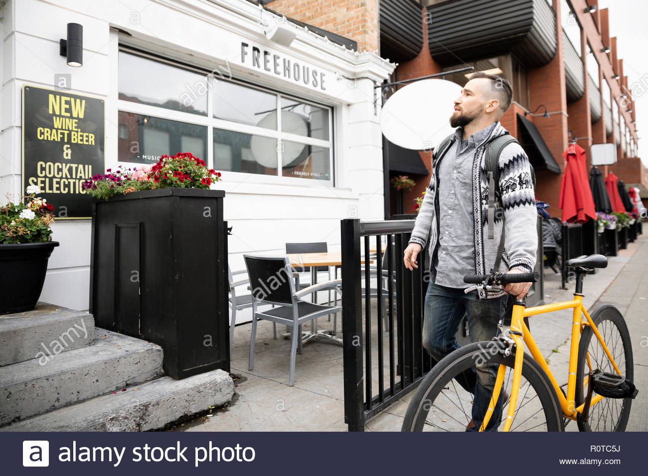 Man with bicycle outside bar - Stock Image