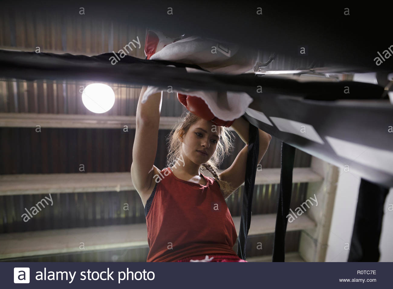 Tough female boxer resting in boxing ring corner - Stock Image