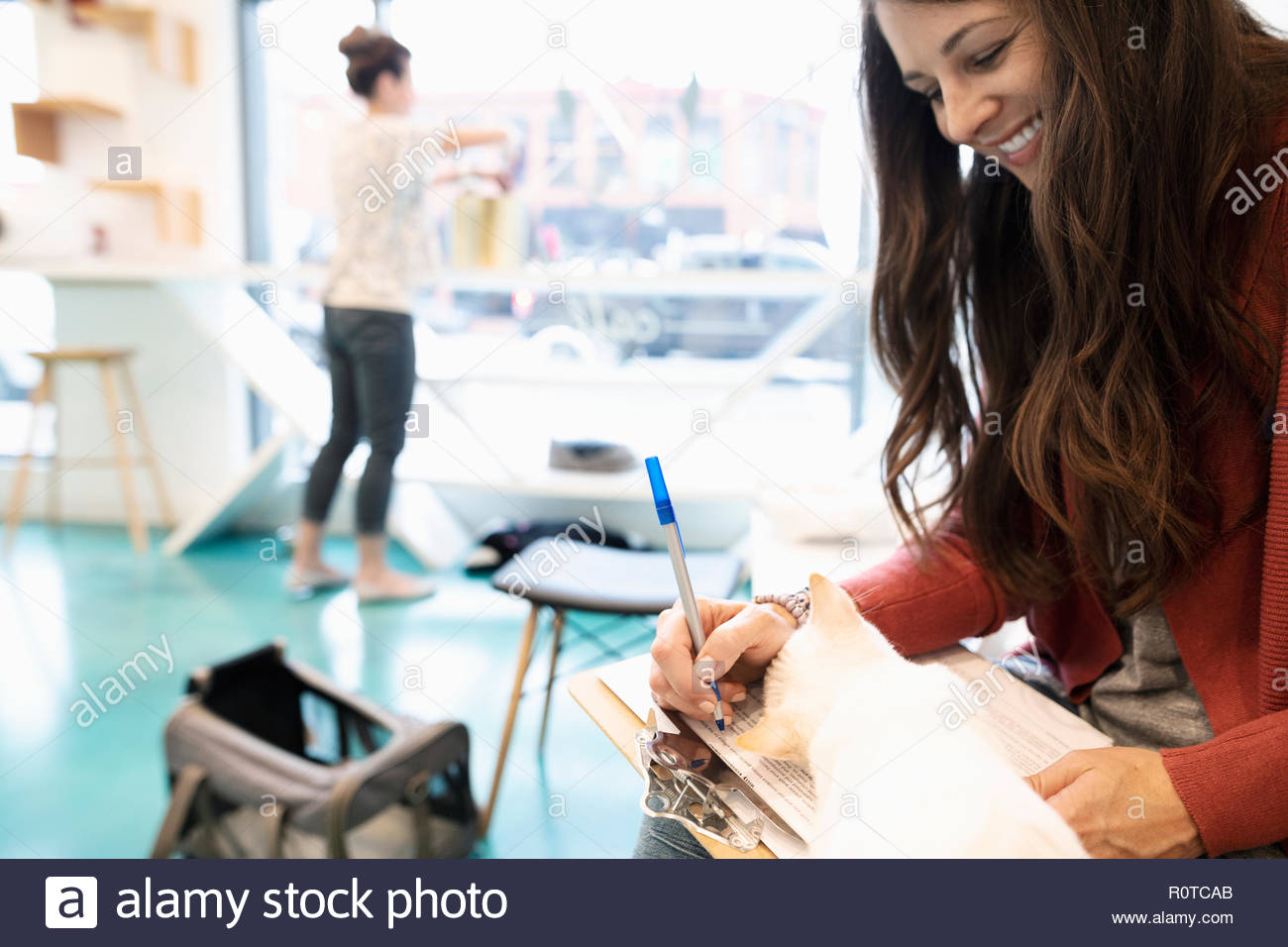 Happy woman adopting kitten, filling out application in cat cafe - Stock Image
