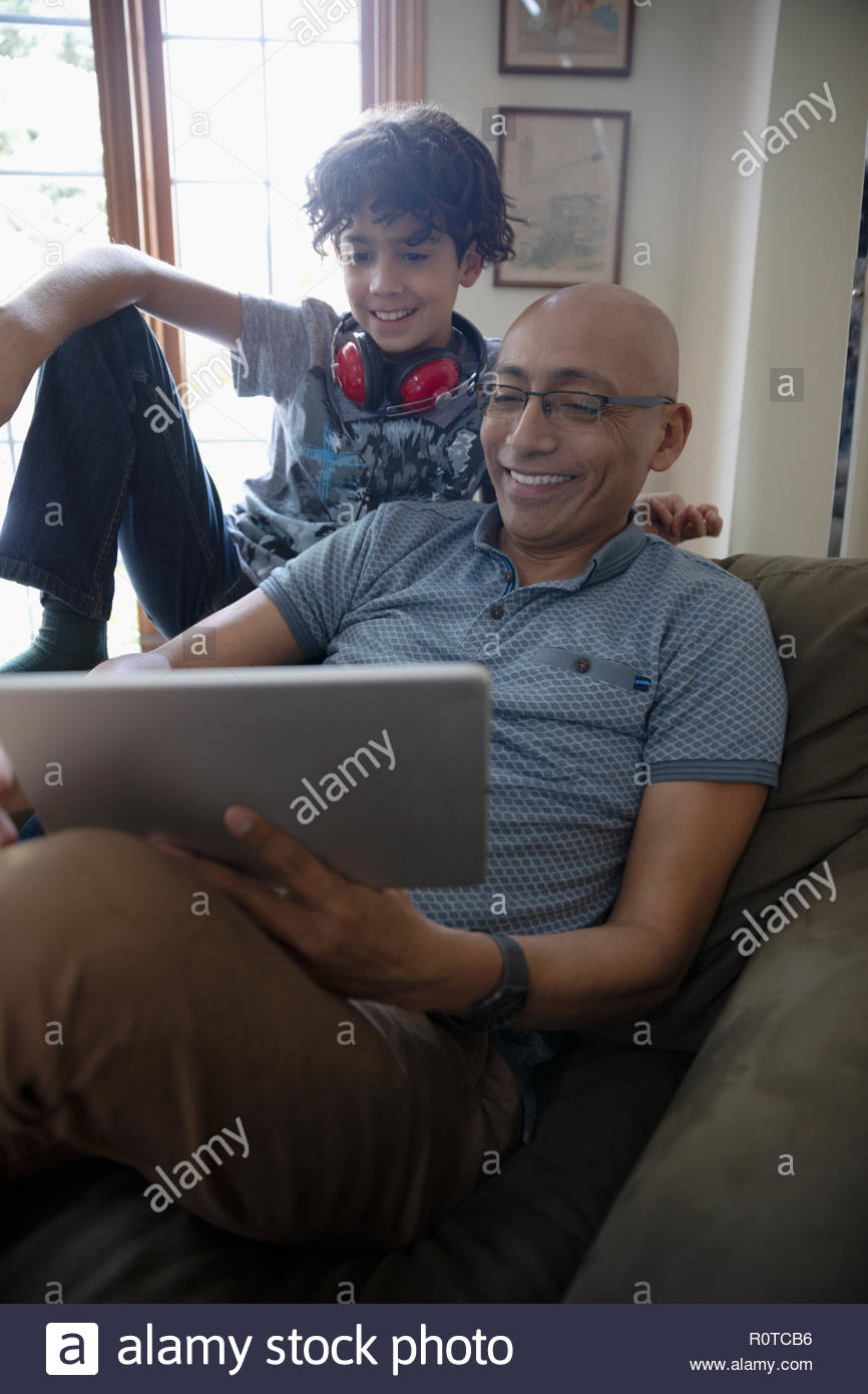 Latinx father and son using digital tablet Stock Photo