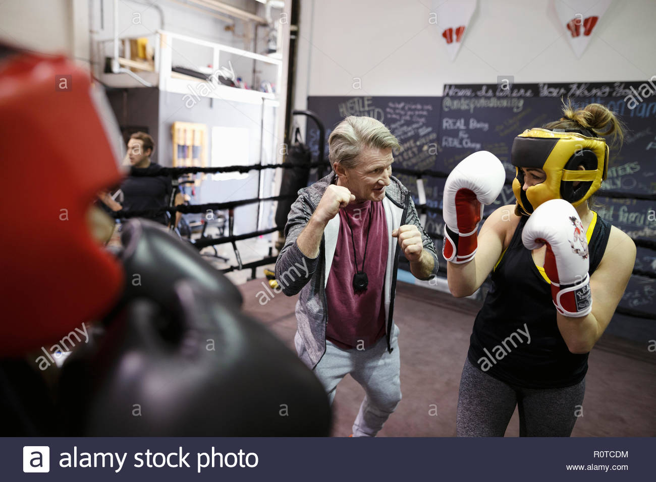 Trainer guiding female boxer training in boxing ring in gym - Stock Image