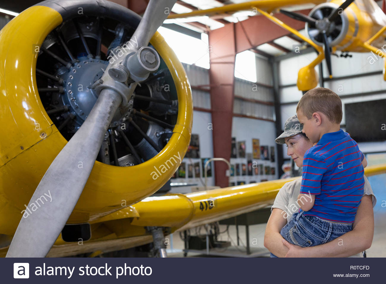 Female army pilot mother showing son airplane in military airplane museum - Stock Image