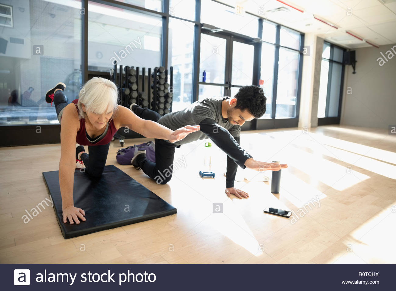 Personal trainer guiding senior woman doing balance stretch in gym studio - Stock Image