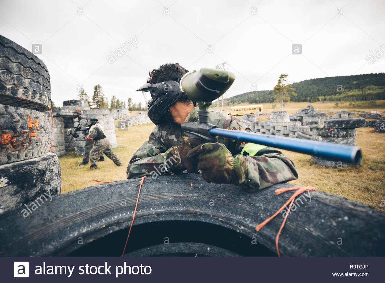 Young man paintballing, aiming gun - Stock Image