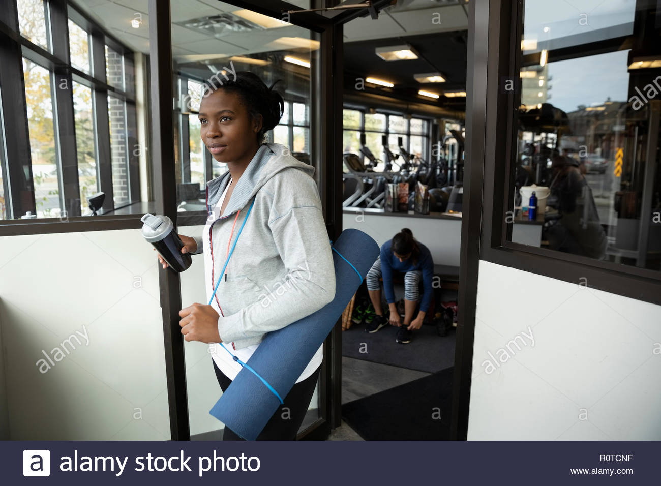 Woman with yoga mat and water bottle leaving gym Stock Photo