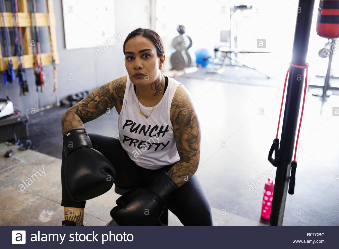 Portrait confident, tough female boxer resting in gym - Stock Image