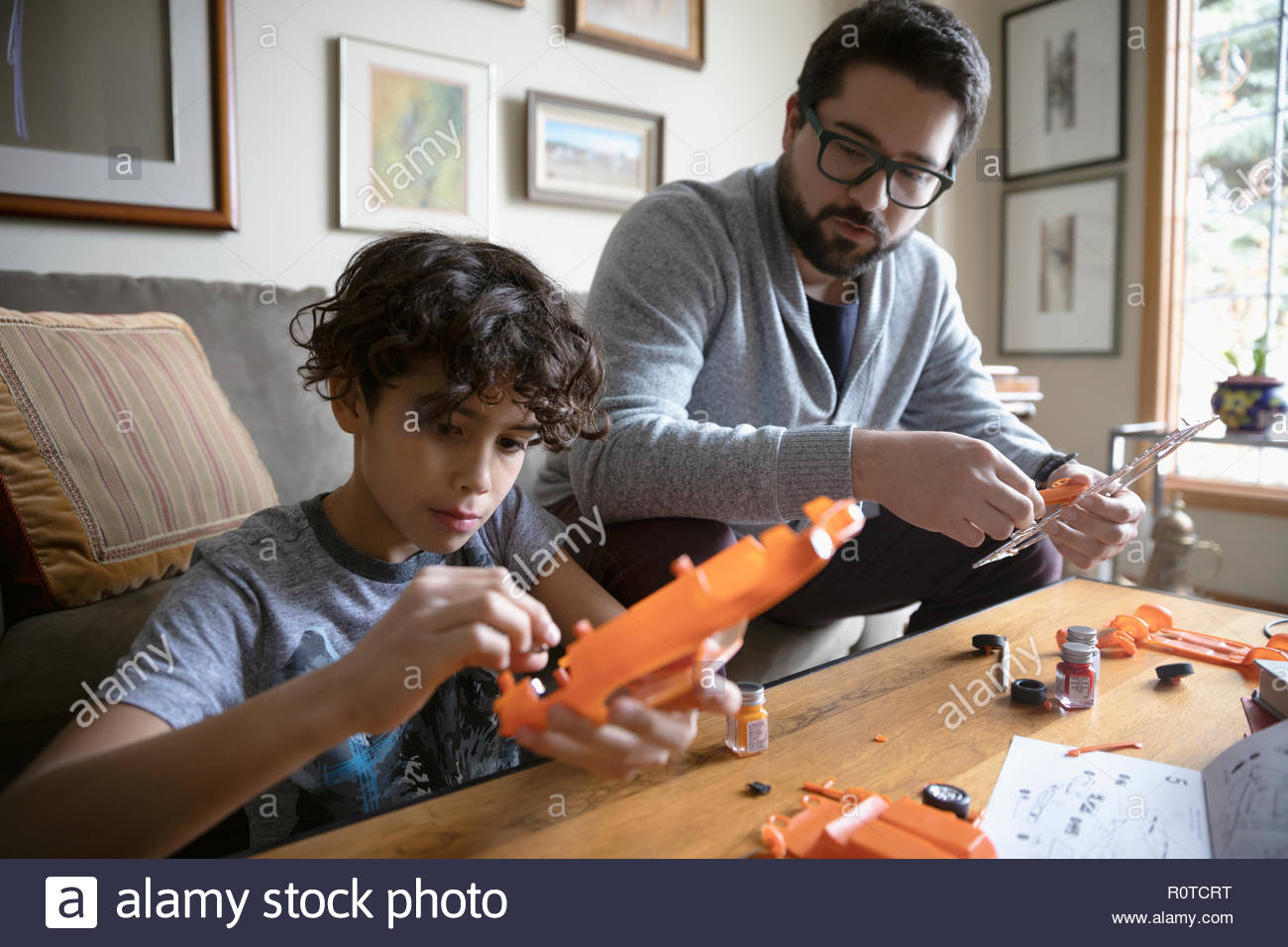 Latinx father and son assembling model car - Stock Image