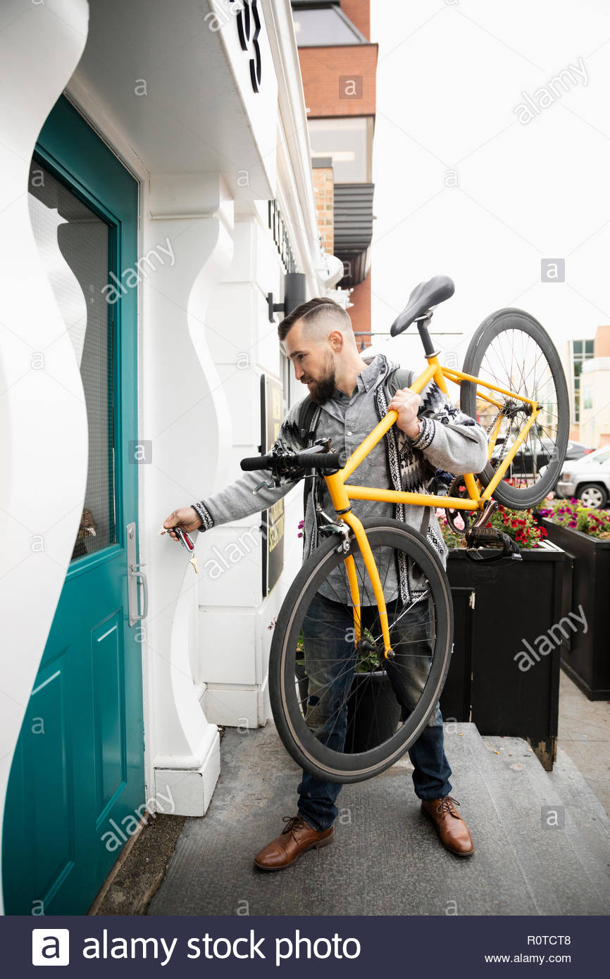 Man with bicycle outside building - Stock Image