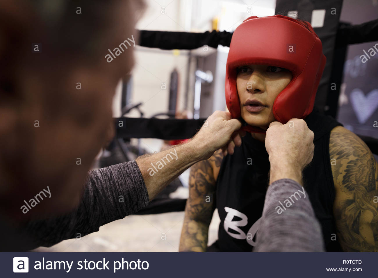 Trainer fastening protective headgear on female boxer - Stock Image