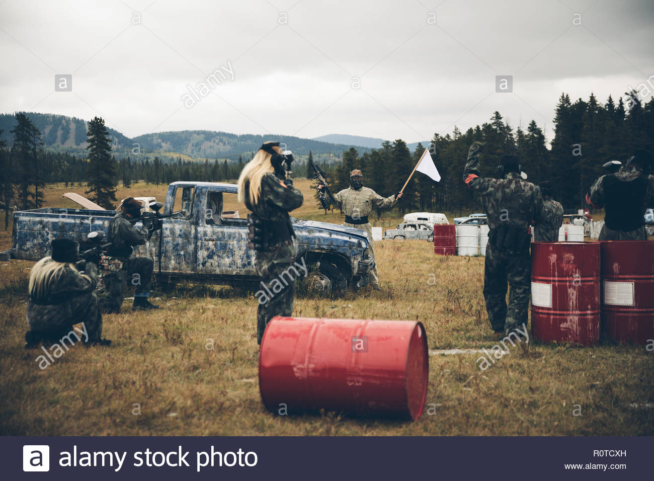 Man waving white flag at paintballing team in field - Stock Image