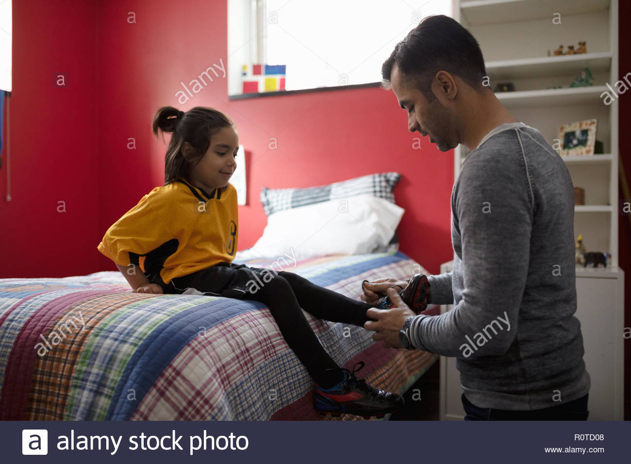 Father tying soccer shoes for son on bed - Stock Image