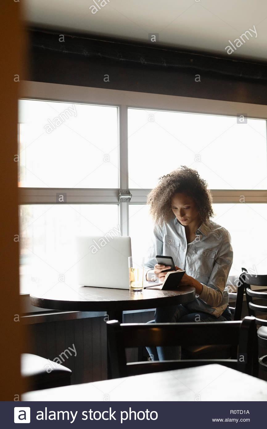 Woman using smart phone at laptop in bar - Stock Image