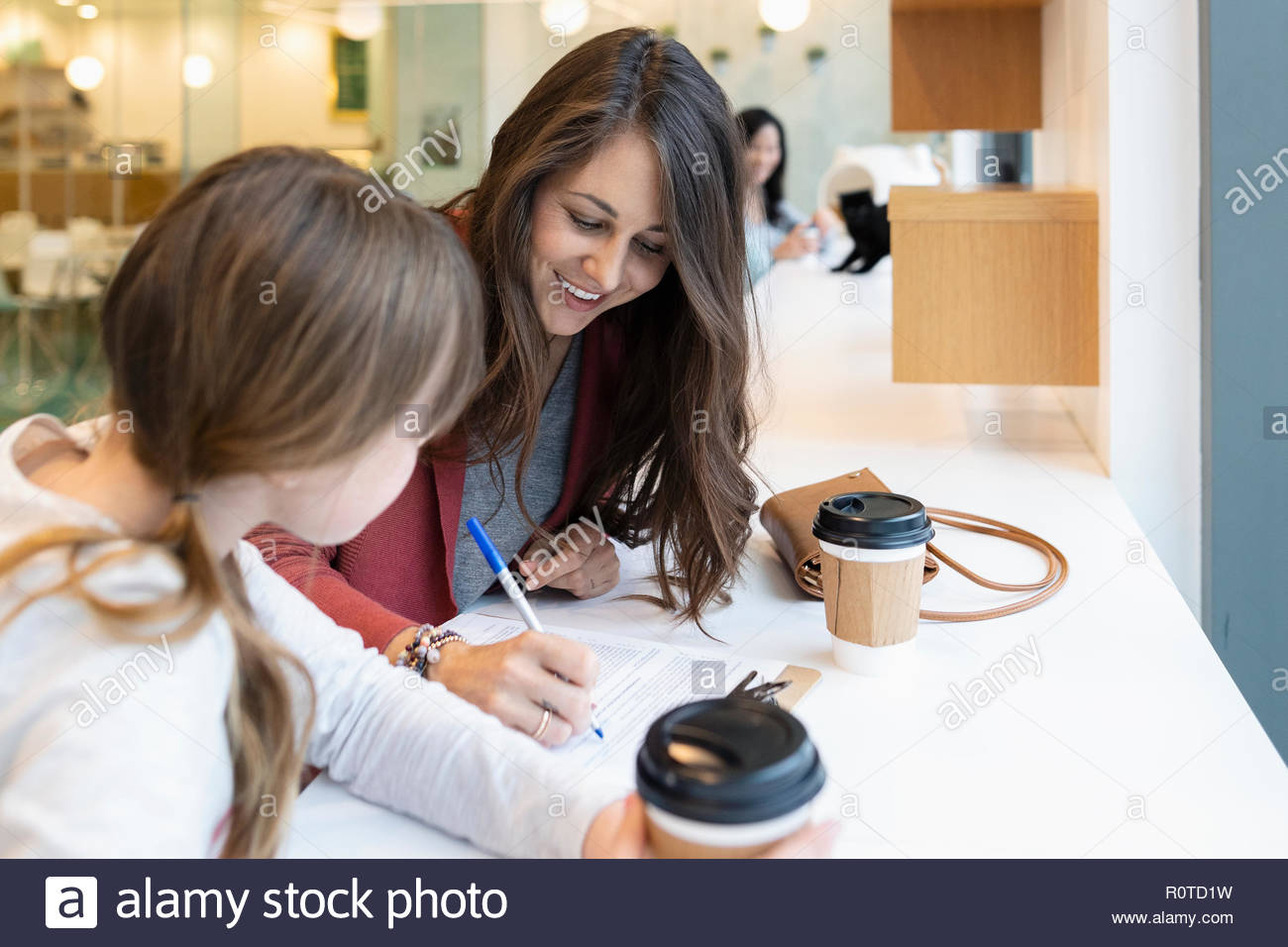 Mother and daughter filling out paperwork in cafe - Stock Image