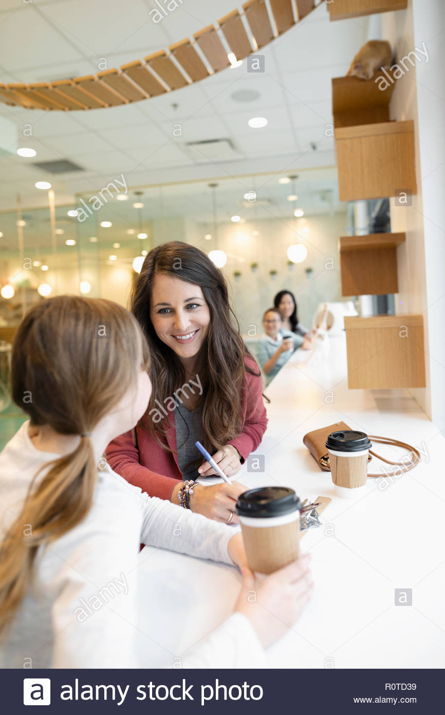 Mother and daughter filling out adoption application and drinking coffee in cat cafe - Stock Image