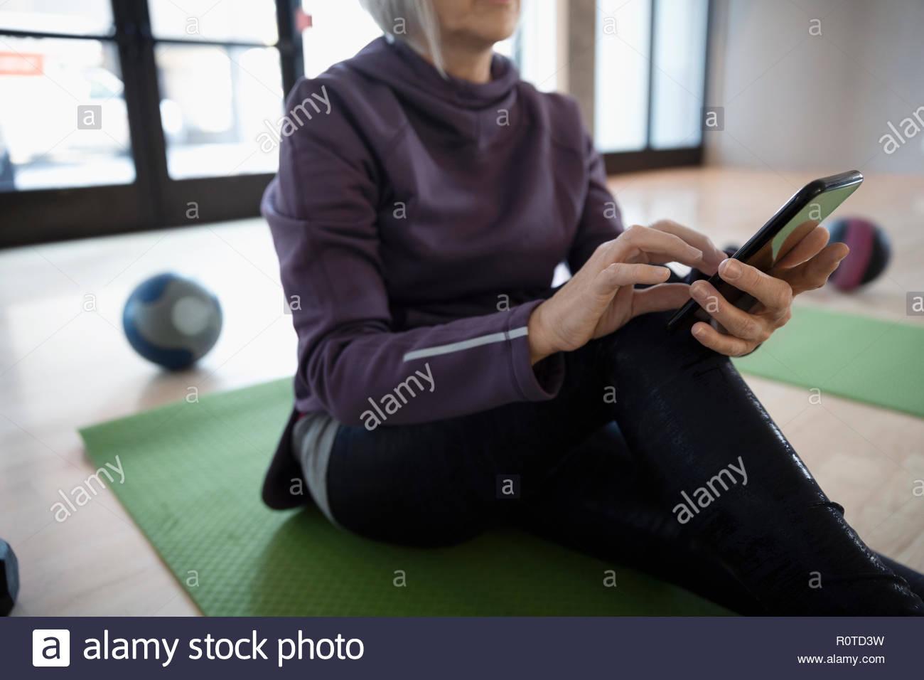 Senior woman using smart phone in gym studio - Stock Image