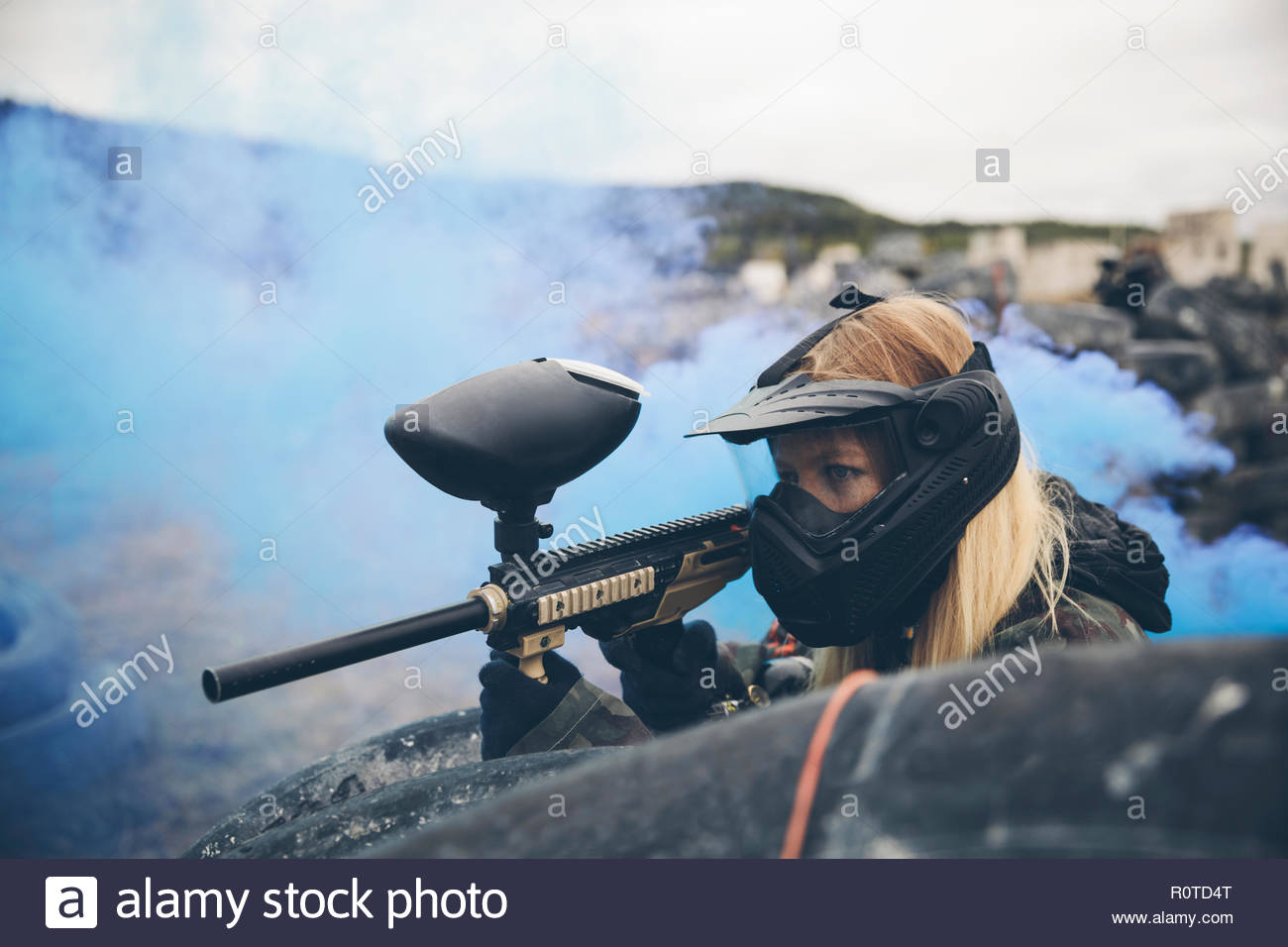 Focused woman paintballing - Stock Image
