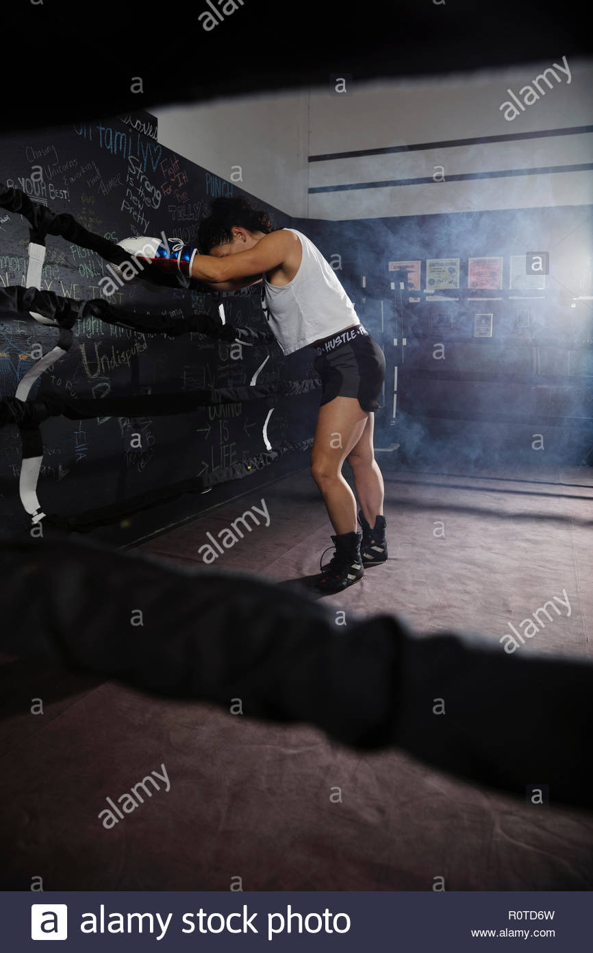 Tired female boxer resting in boxing ring Stock Photo