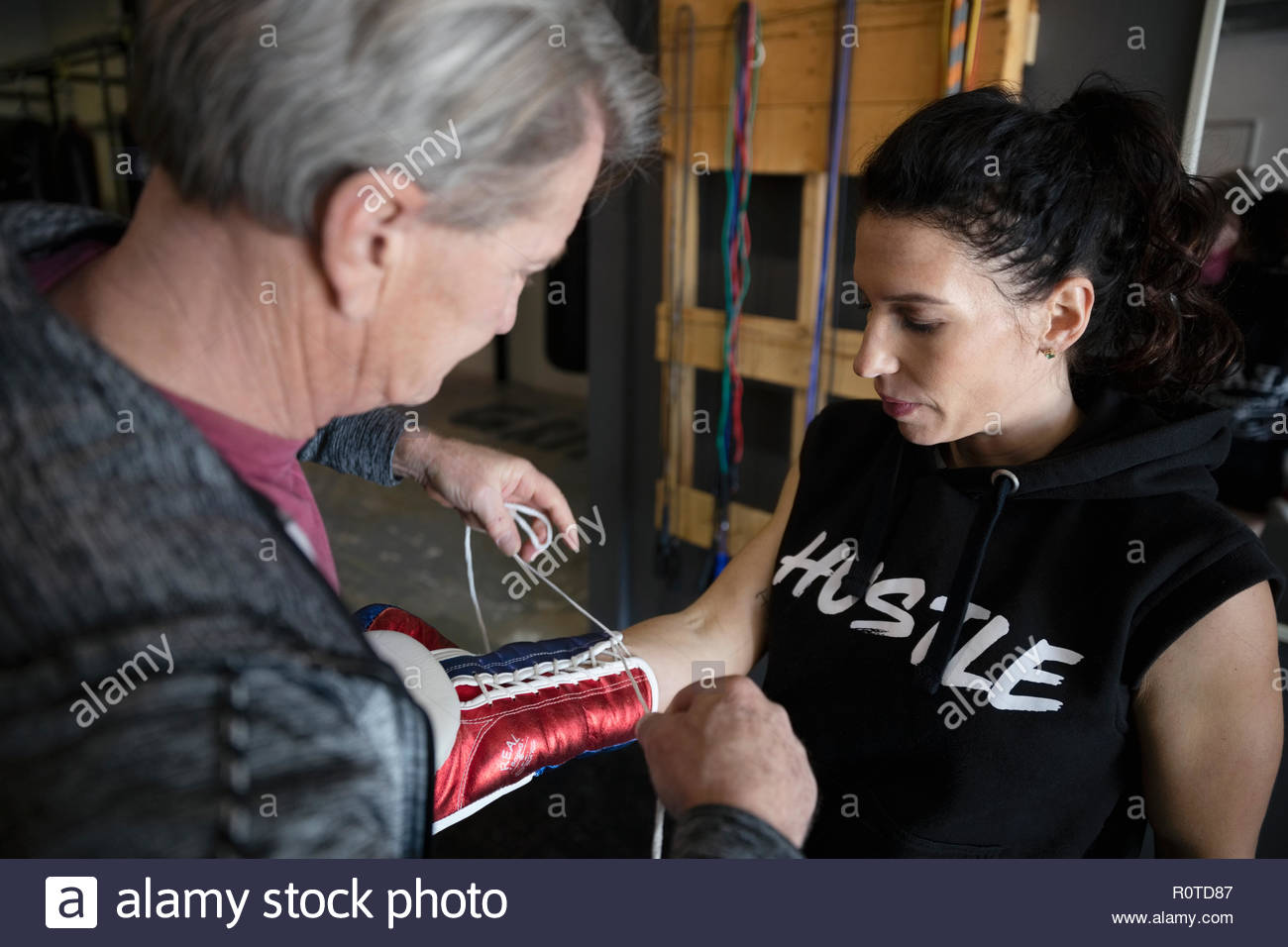 Trainer helping female boxer lacing boxing gloves in gym Stock Photo